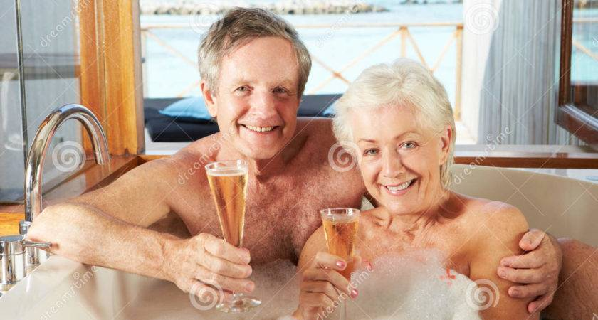 Senior Couple Relaxing Bath Drinking Champagne Together